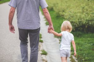 Elderly man holding child's hand walking