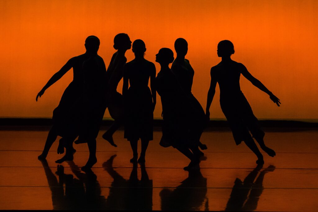 Silhouette of dancers with orange background